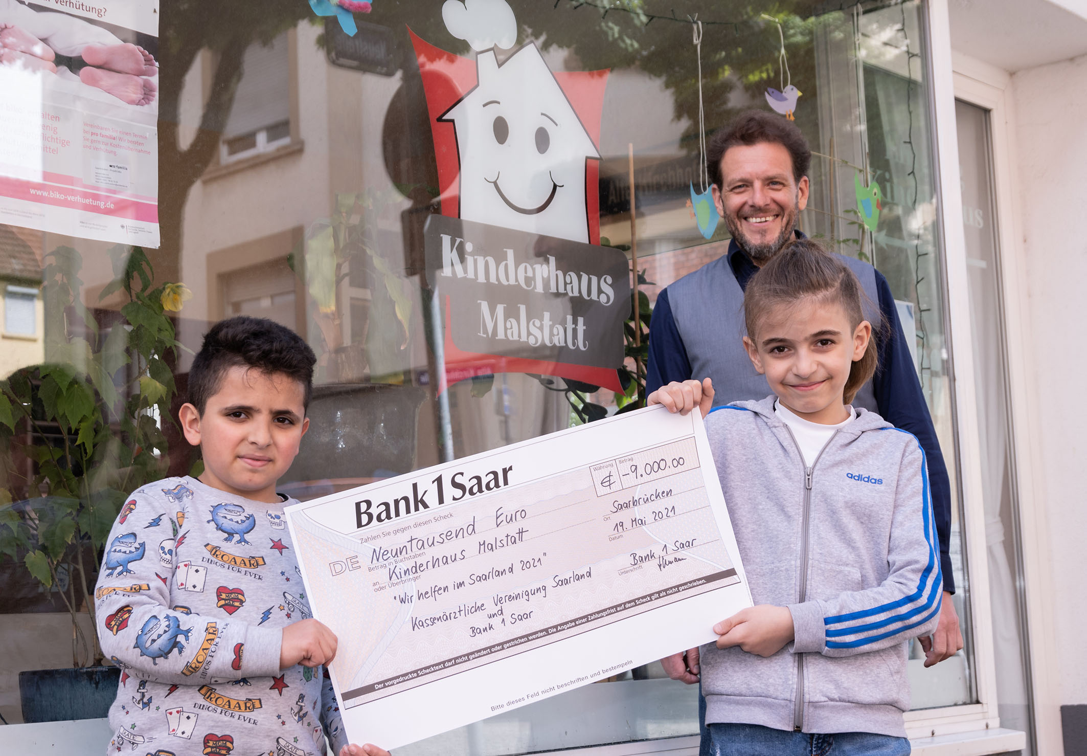 Carsten Freels, Leiter des Kinderhauses, freut sich mit den Kindern über die tolle Spende.