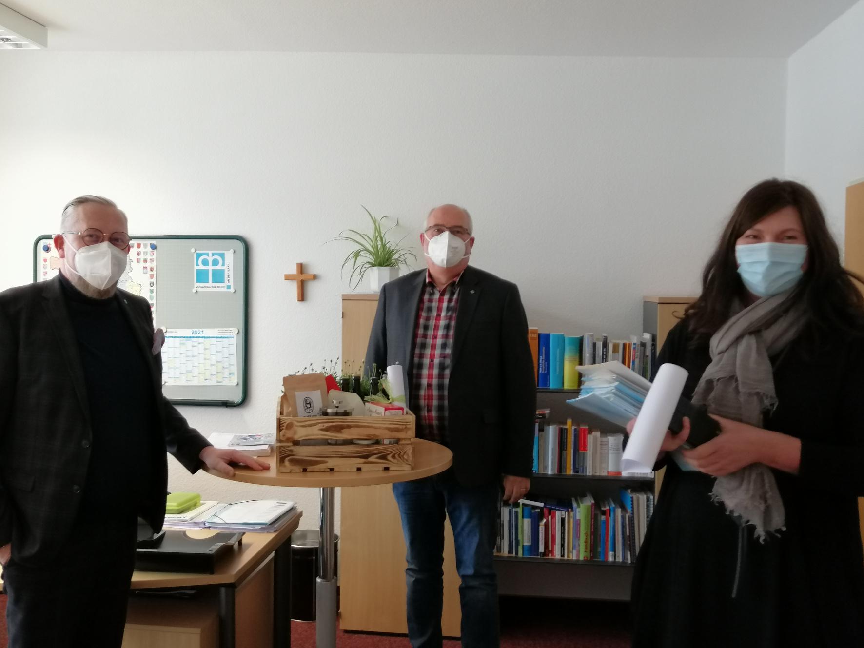"""Anne Fennel und Oliver Kremp-Mohr dankten Udo Blank für die gute Zusammenarbeit und überreichten augenzwinkernd ein """"Diakonie Überlebenspaket""""."""