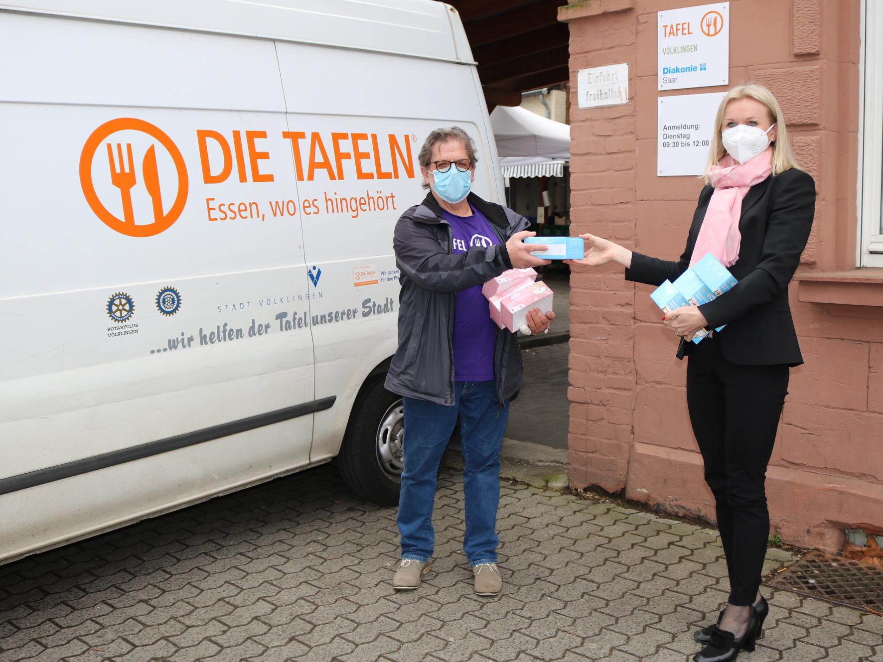 Reinhard Daschmann (l.) nimmt die Maskenspende von Katarzyna Schott entgegen. Foto: Diakonie Saar/Stein