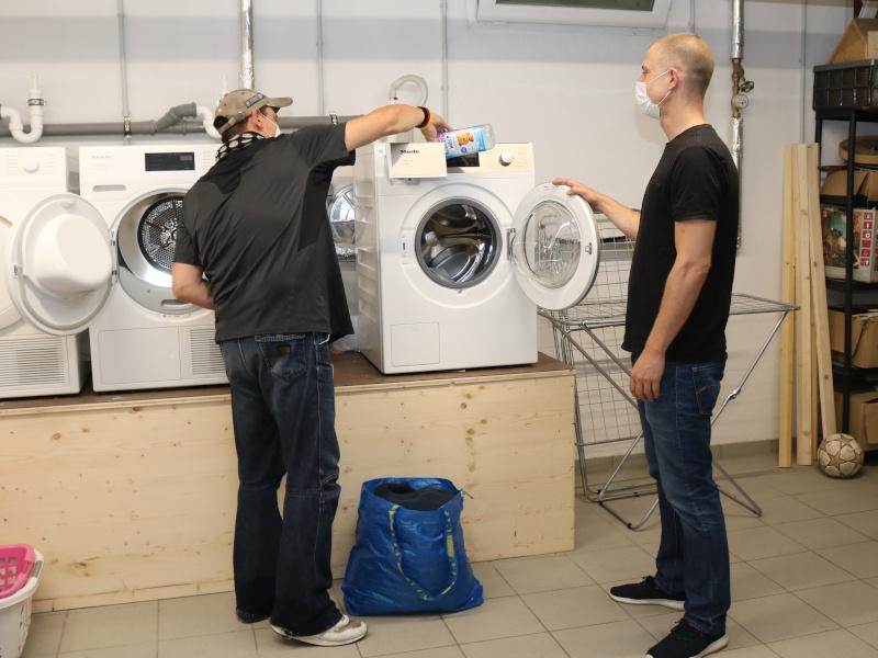 Die Mitarbeitenden unterstützen die Besuchenden beim Waschen ihrer Wäsche. Fotos: Diakonie Saar /Stein