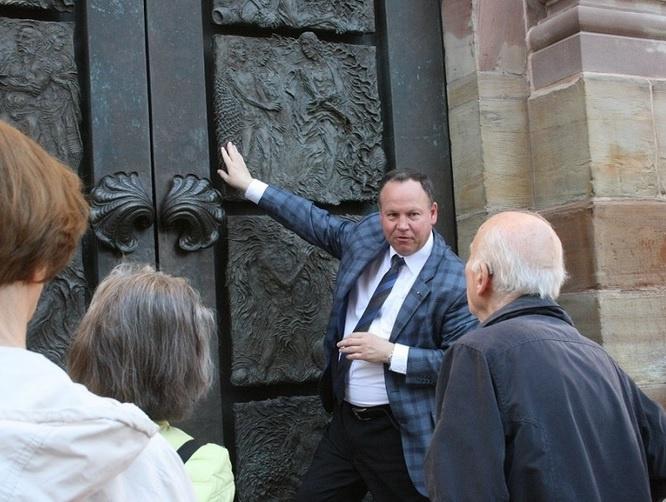 Prof. Dr. Joachim Conrad erläutert vor einer Gruppe die Besonderheiten des Portals an der Basilika St. Johann, Foto: evks/Eulenstein