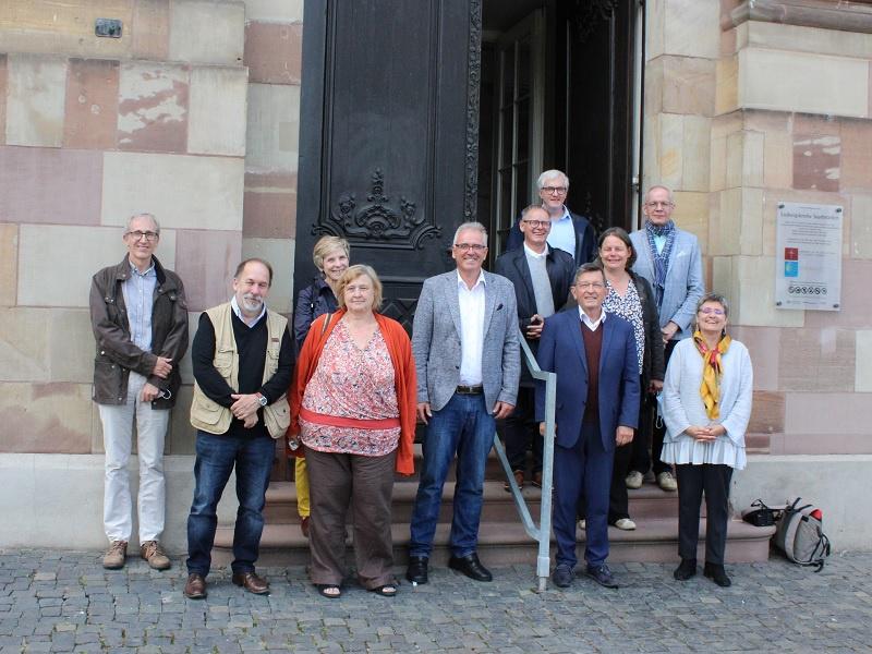 Pfarrer Dr. Thomas Bergholz (l.) und Kirchenrat Frank-Matthias Hofmann (5.v.l.) begrüßten die französische Delegation um UEPAL-Präsident Christian Albecker (4.v.r.) an der Ludwigskirche