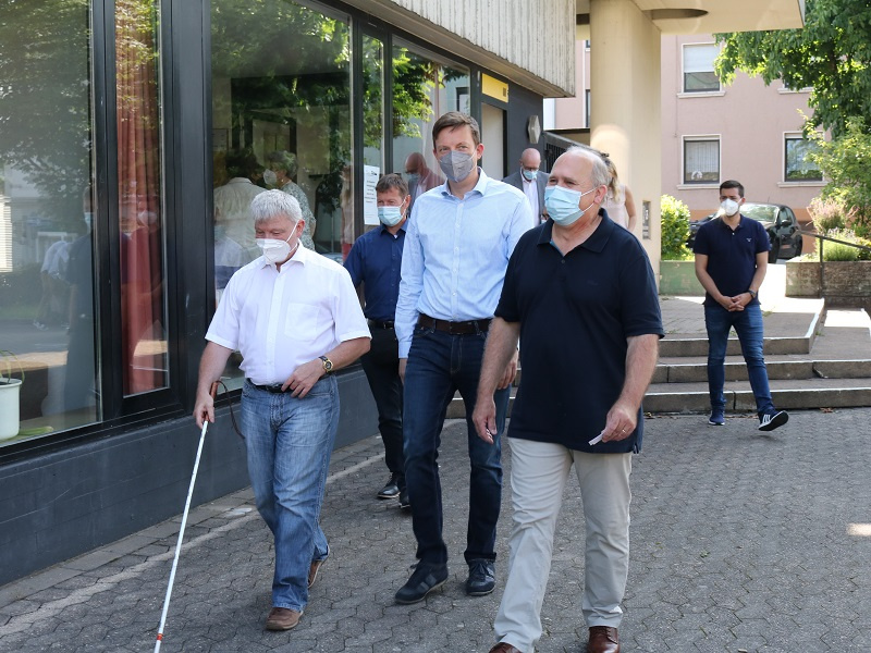 Pfarrer Josef Jirasek (r.) und Ehrenamtlicher Heinz-Peter Engels (l.) führen Ministerpräsident Tobias Hans (M.) zum 'Vier-Sinne'-Café, Foto: Diakonie/Stein