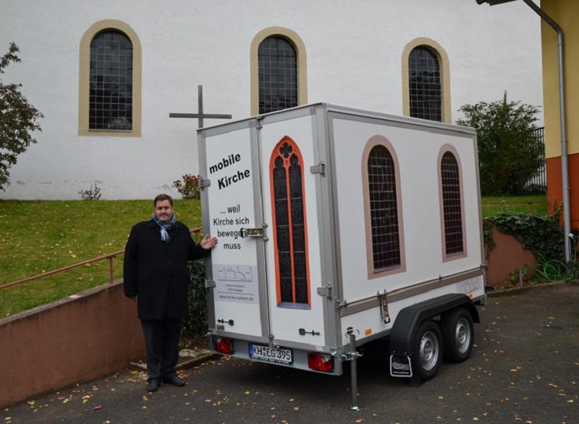 Der Anhänger der mobilen Kirche erinnert an die Roxheimer Kirche (im Hintergrund). Foto: Dieter Ackermann