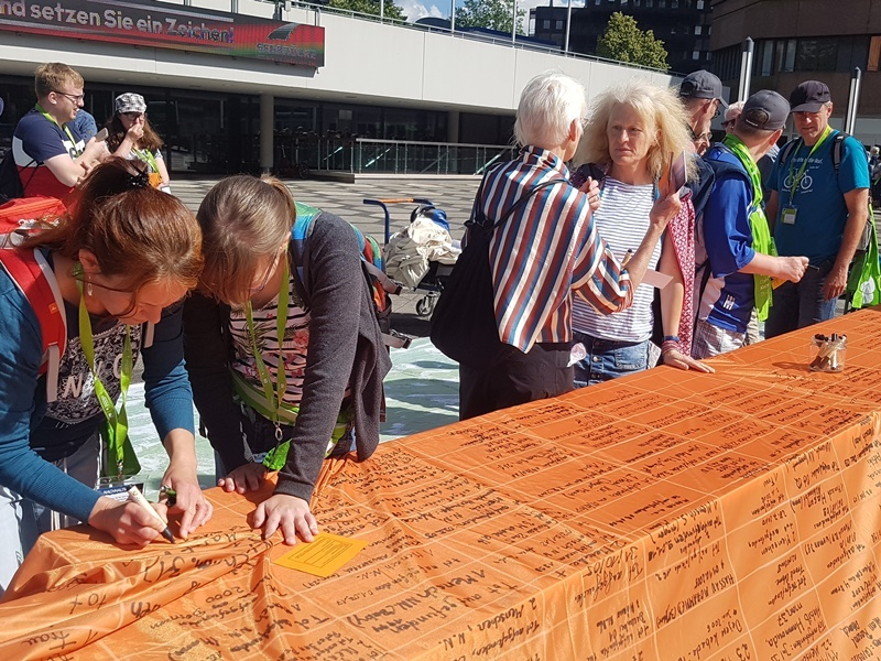 Zwei Tage lang schrieben Passantinnen und Passanten in der Dortmunder Innenstadt die Namen der im Mittelmeer Ertrunkenen auf Transparente. Die Banner hingen anschließend an der Reinoldikirche. Foto: e